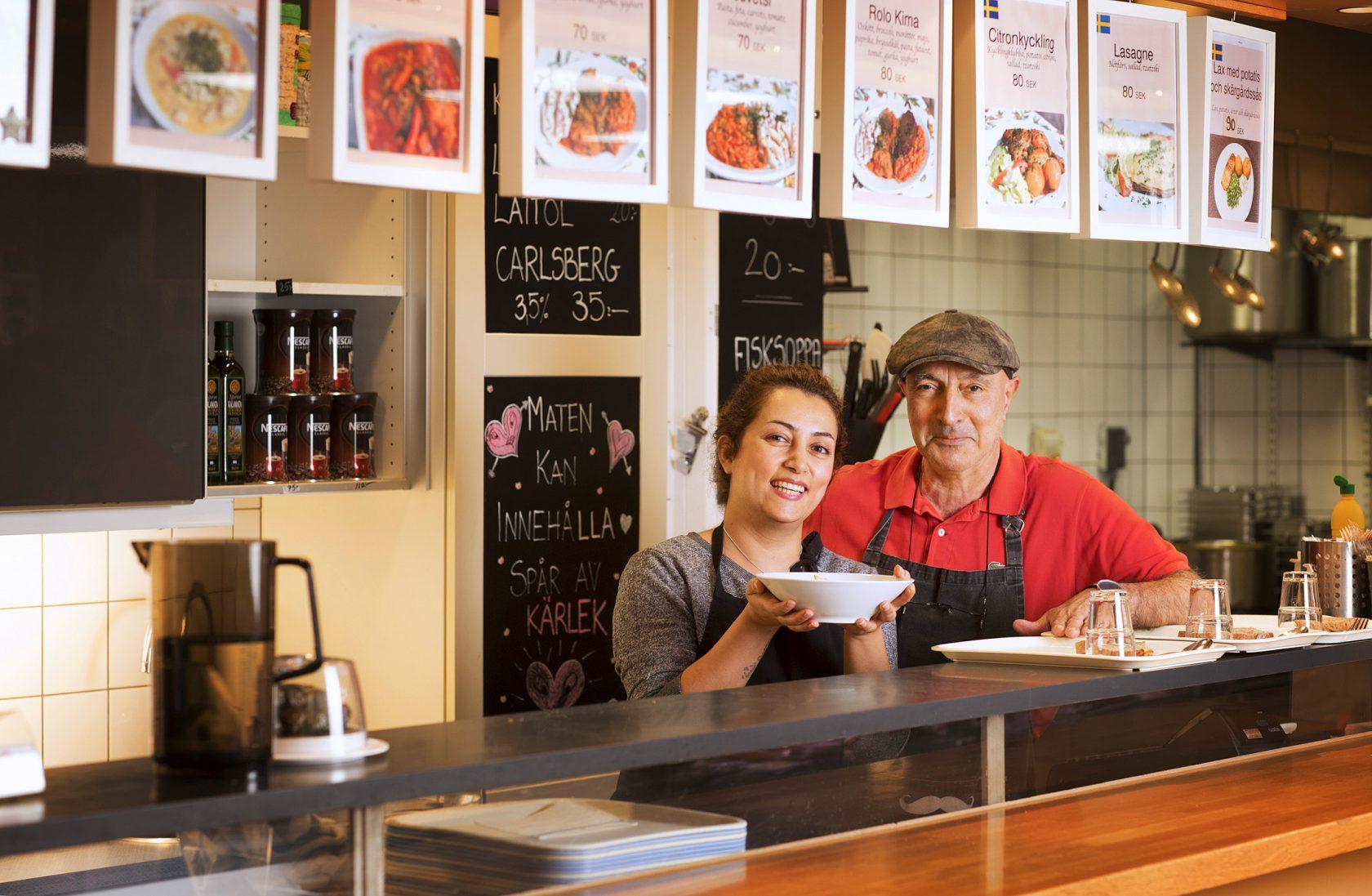 En man och en kvinna står bakom en butiksdisk med en upphälld tallrik soppa.