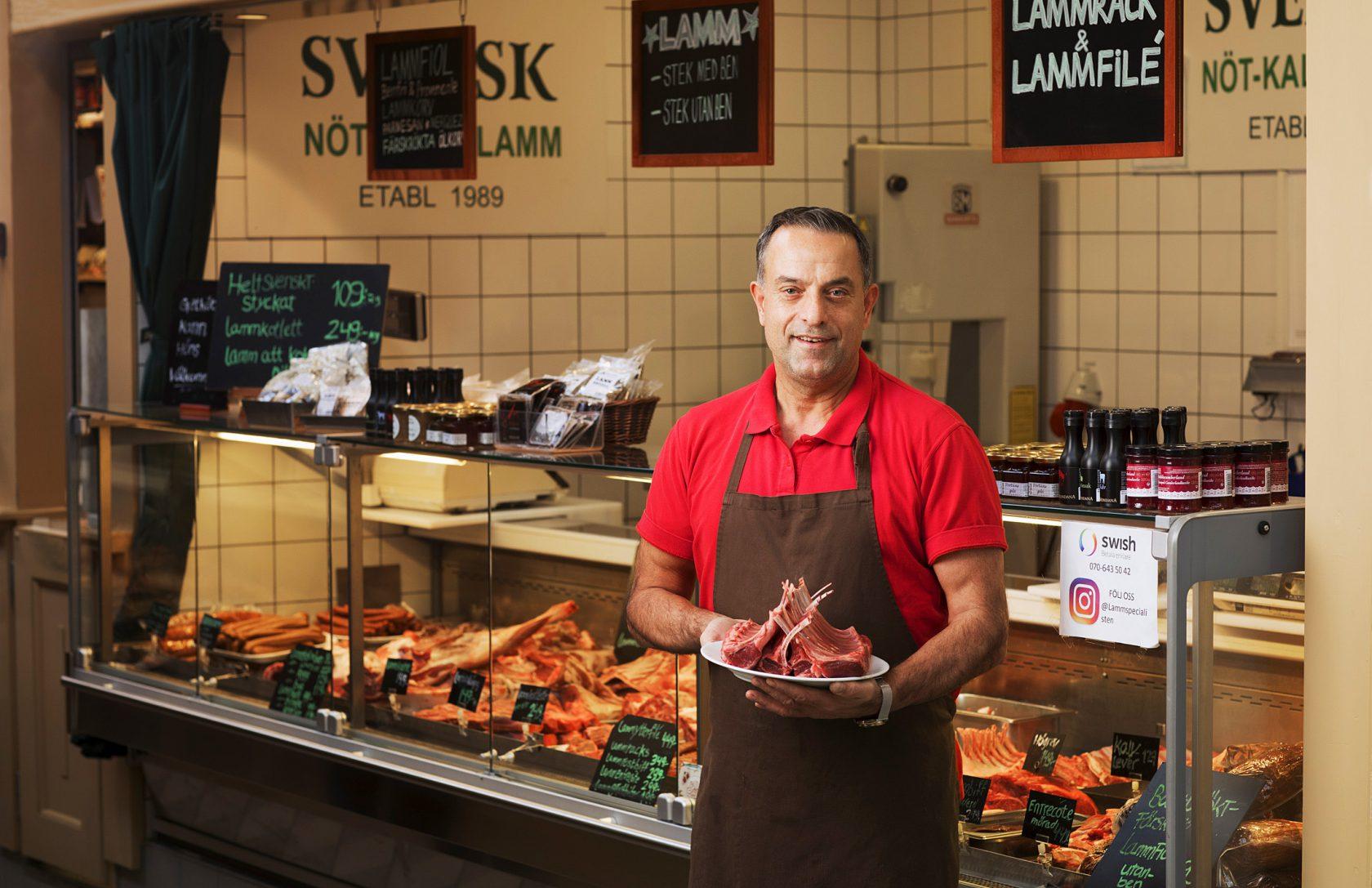 En man står framför en butiksdisk med en tallrik med kött.