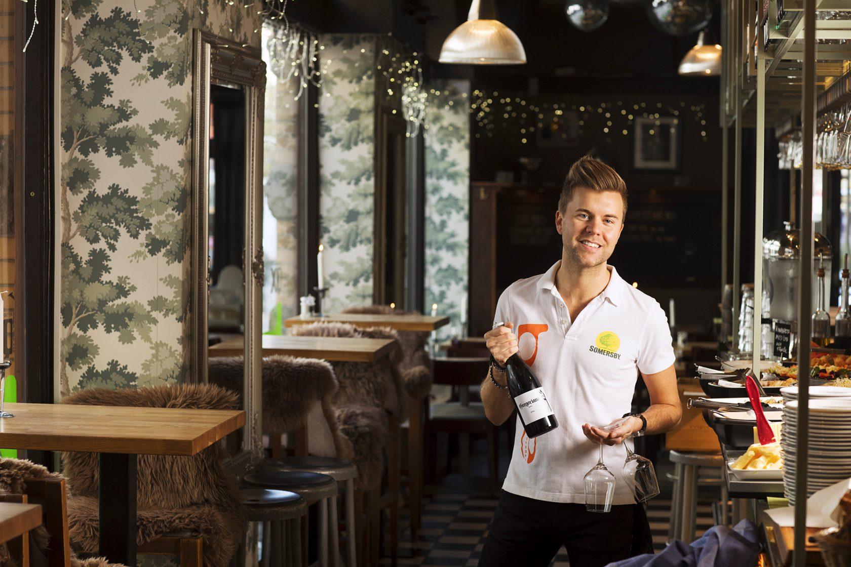 En man står i en restaurang och håller i en vinflaska och ett glas.