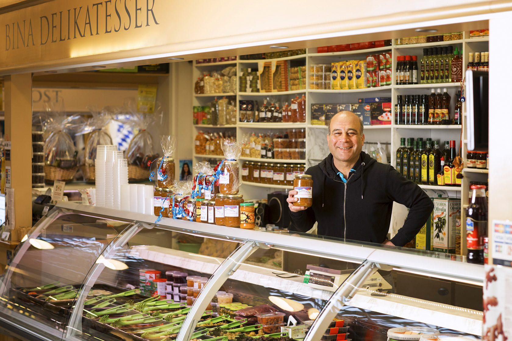 En man står bakom en butiksdisk och håller upp en glasbruk med delikatesser.