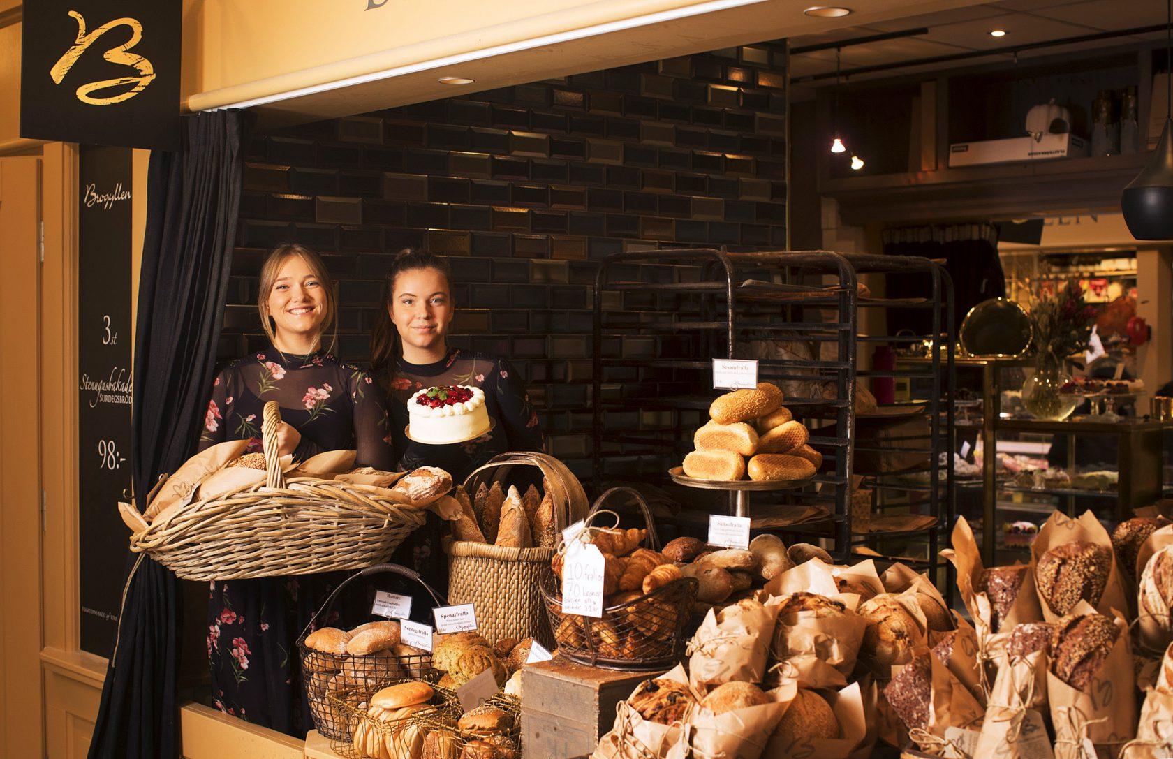 Två kvinnor står i en brödbutik och håller upp en korg med bröd och en tårta.
