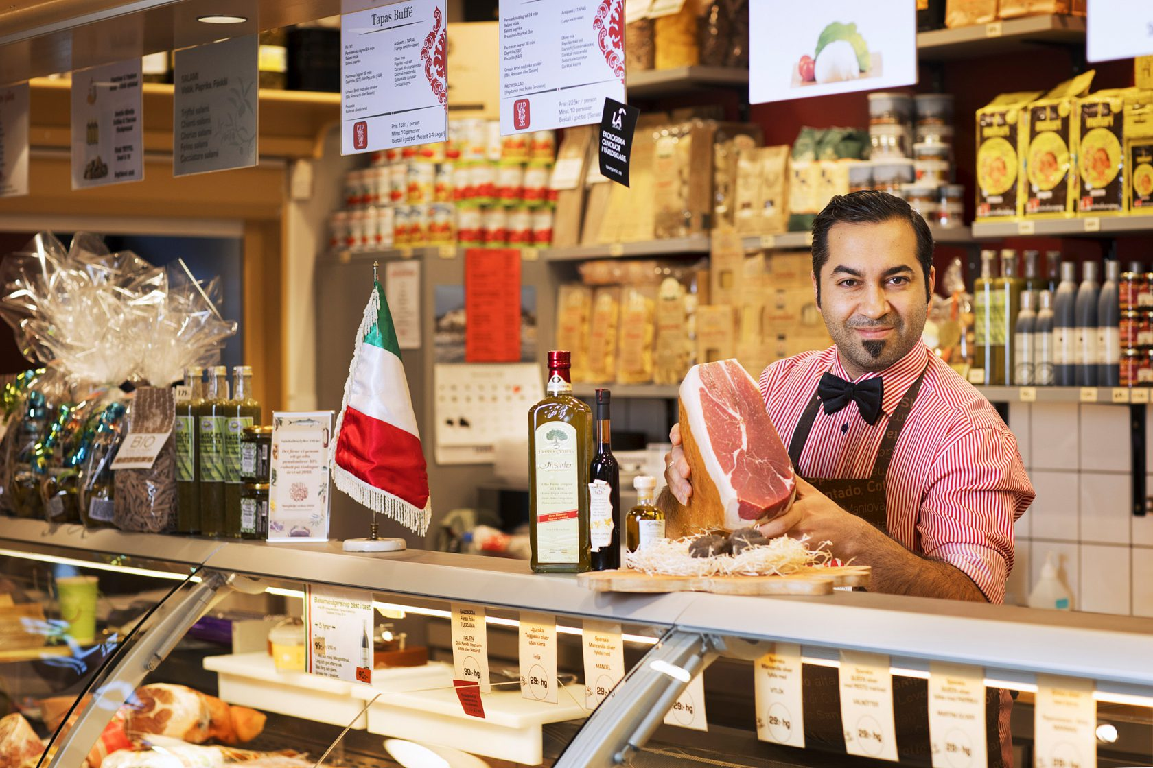 En man står bakom en butiksdisk och håller upp delikatesser.