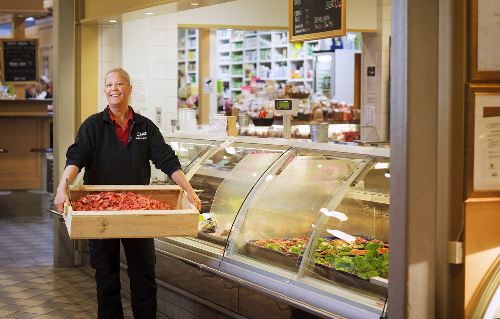 En kvinna står framför en butiksdisk och håller i en stor låda med skaldjur.