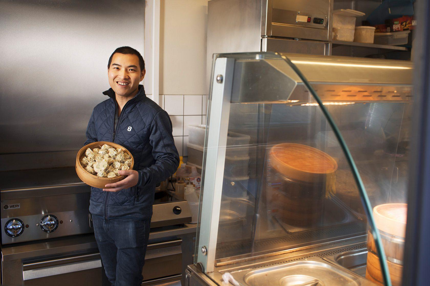En leende man står i ett kök och håller upp en korg med dumplings.