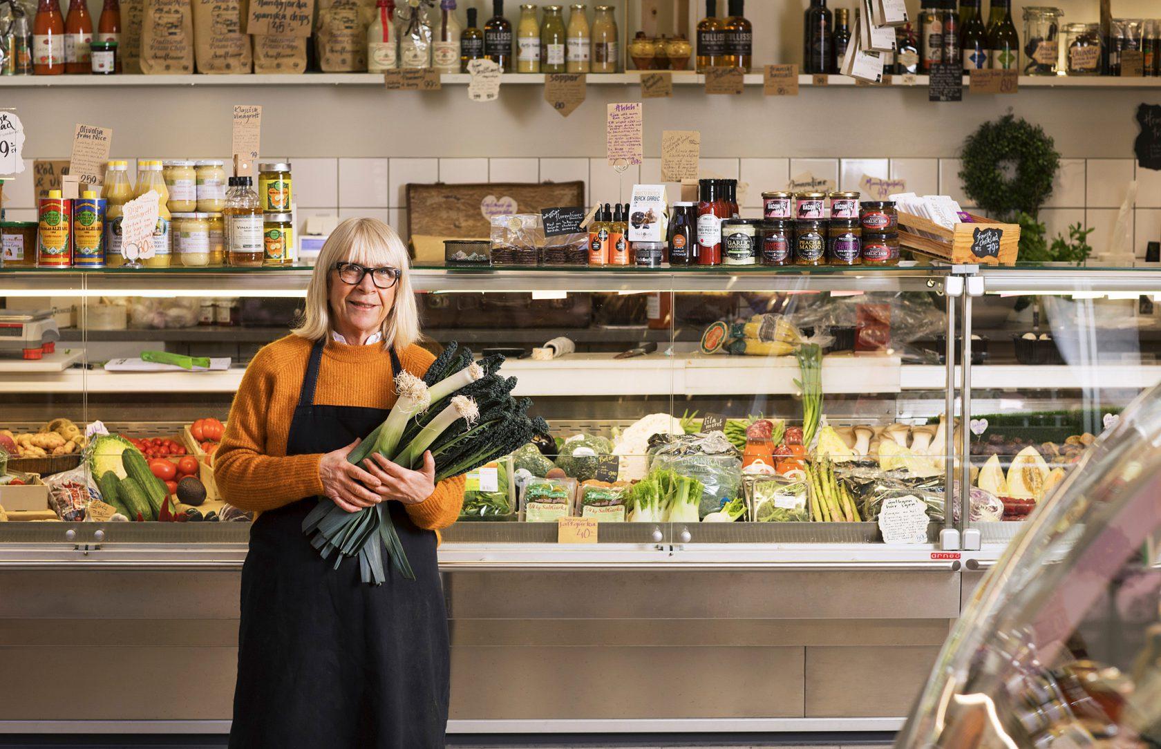 En kvinna står framför en butik och håller i ett knippe grönsaker.