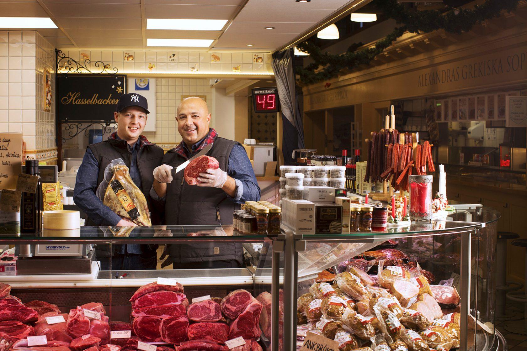 Två män står bakom en köttdisk och håller upp stycken med kött i händerna.