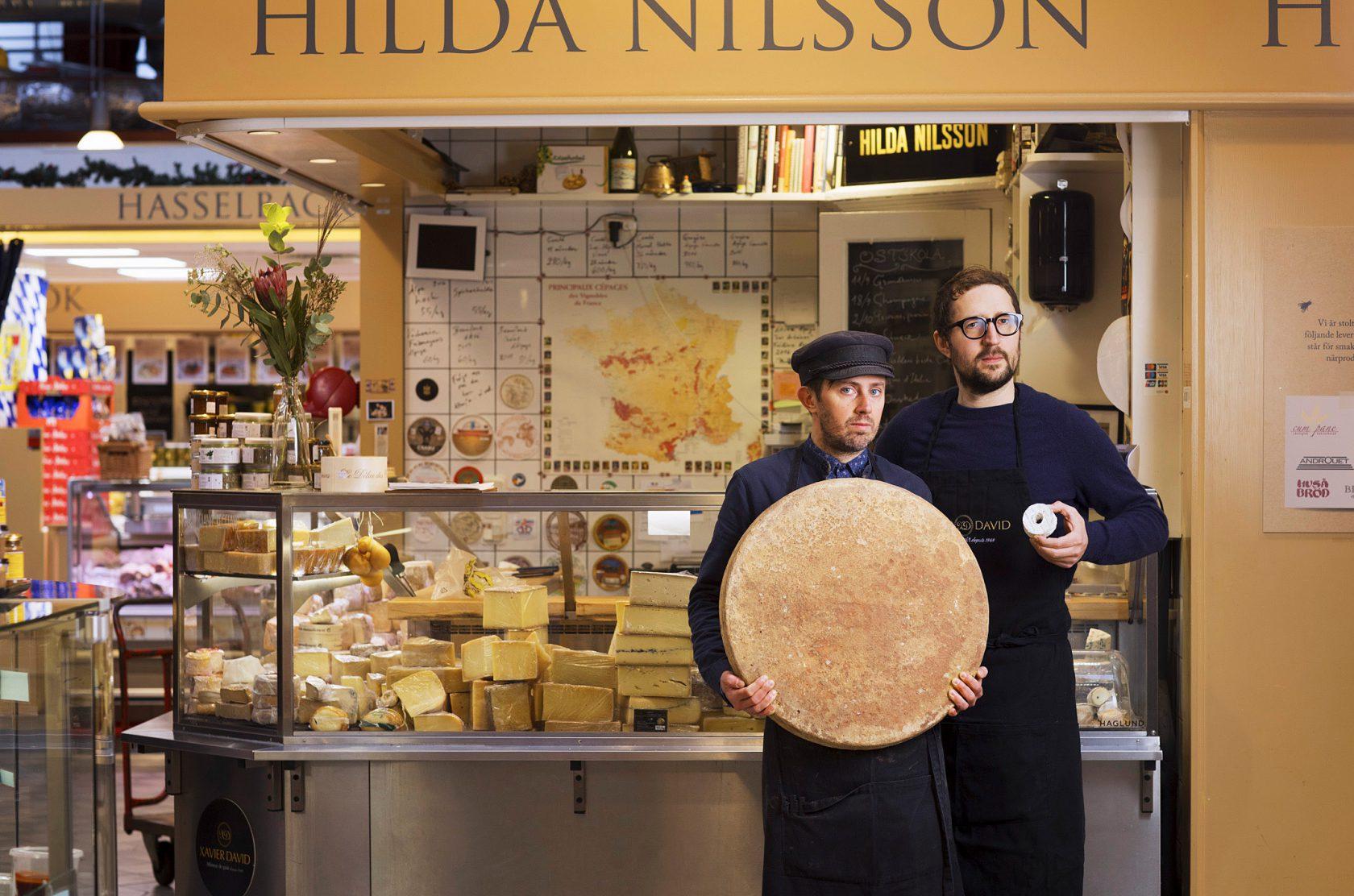 Två män står framför sin ostbutik med en stor och en liten ost i händerna.