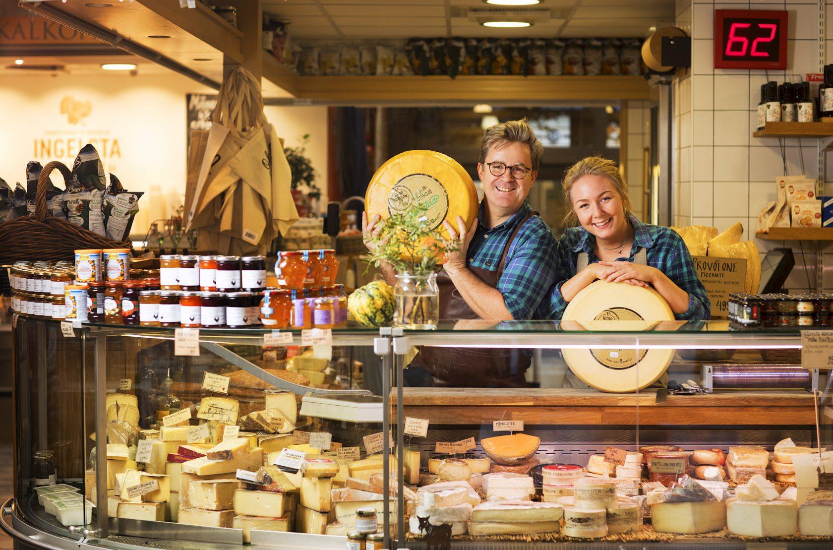 En man och en kvinna står med två stora ostar i händerna bakom en ostdisk.