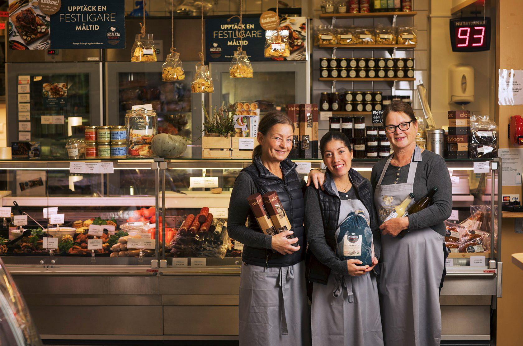 Tre kvinnor står och håller upp olika matprodukter framför en handlarbod.