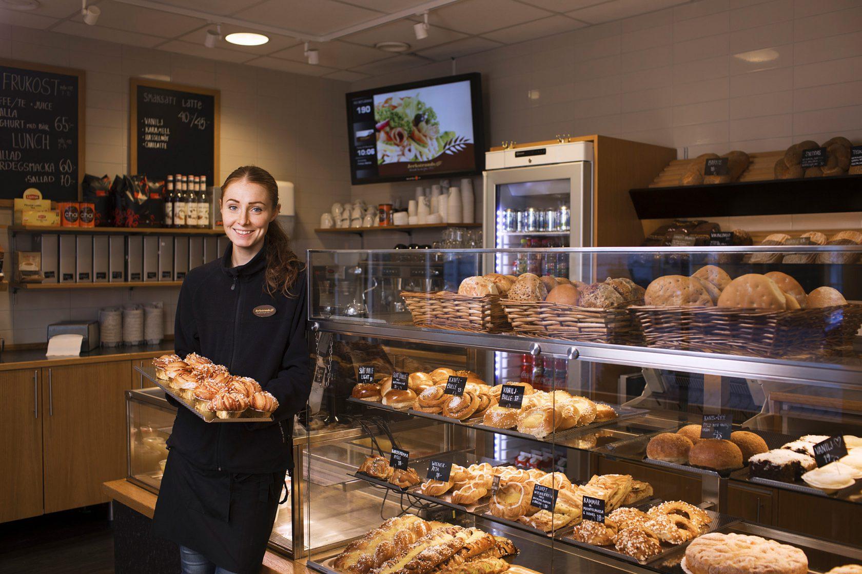 En kvinna i personalen håller upp en bricka med nybakt bröd.