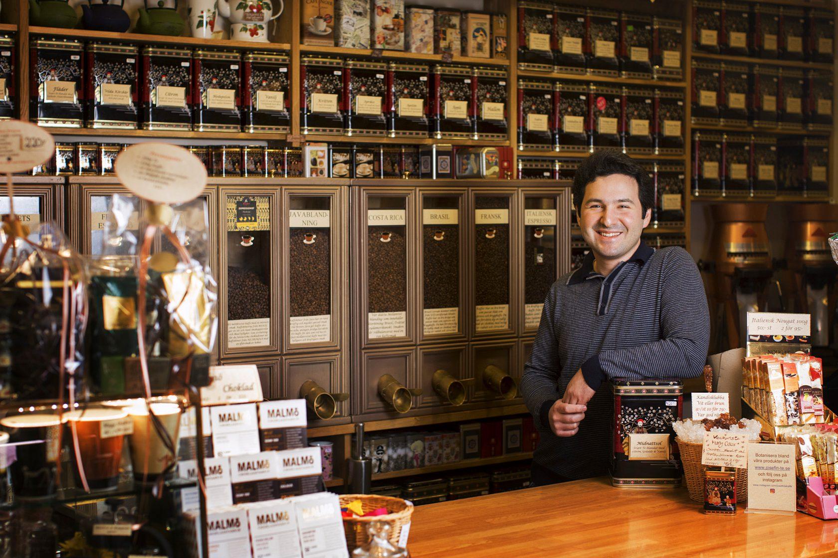 En man står och ler i sin te- och kaffehandel.