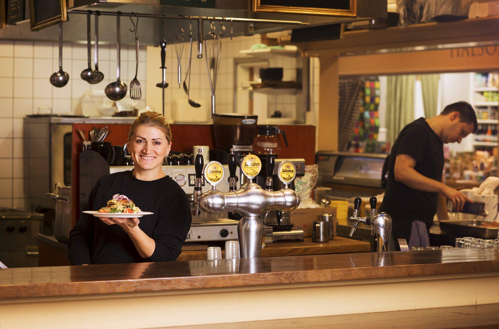 En kvinna står bakom en disk och håller upp en tallrik med mat.