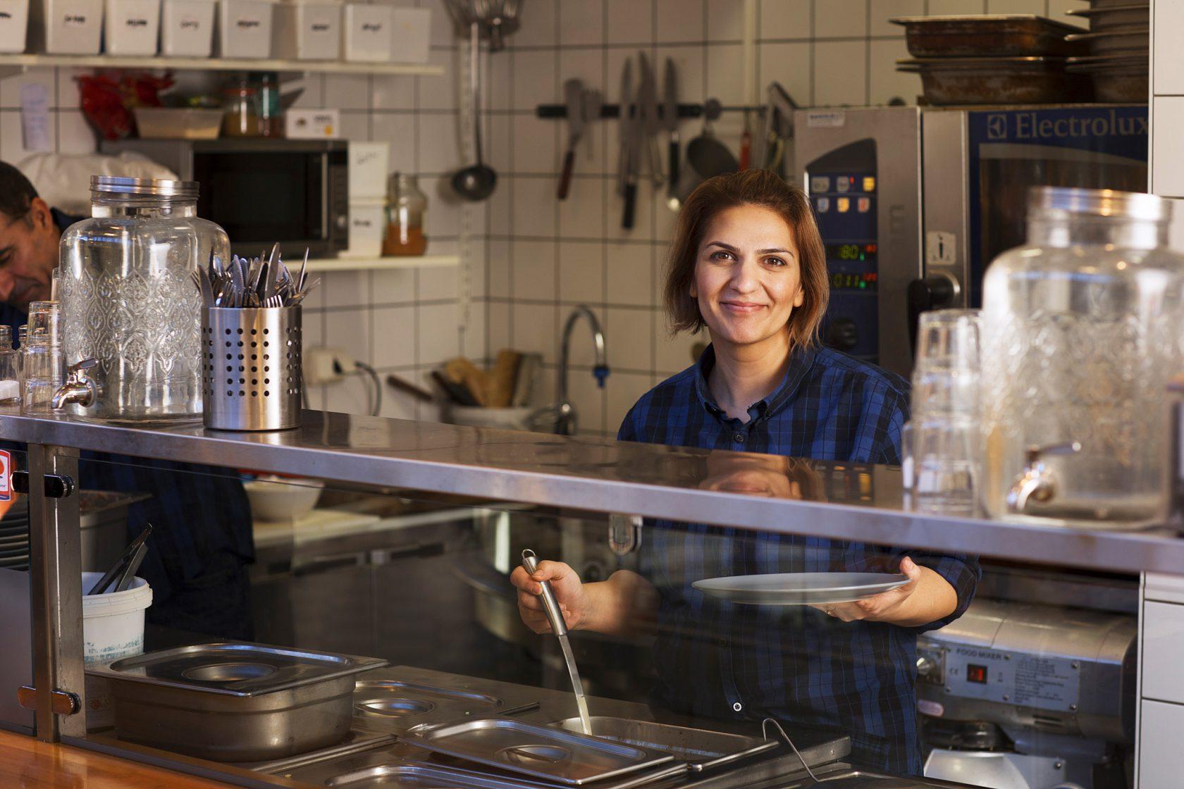 En kvinna står bakom en disk beredd att lägga upp mat på en tallrik.