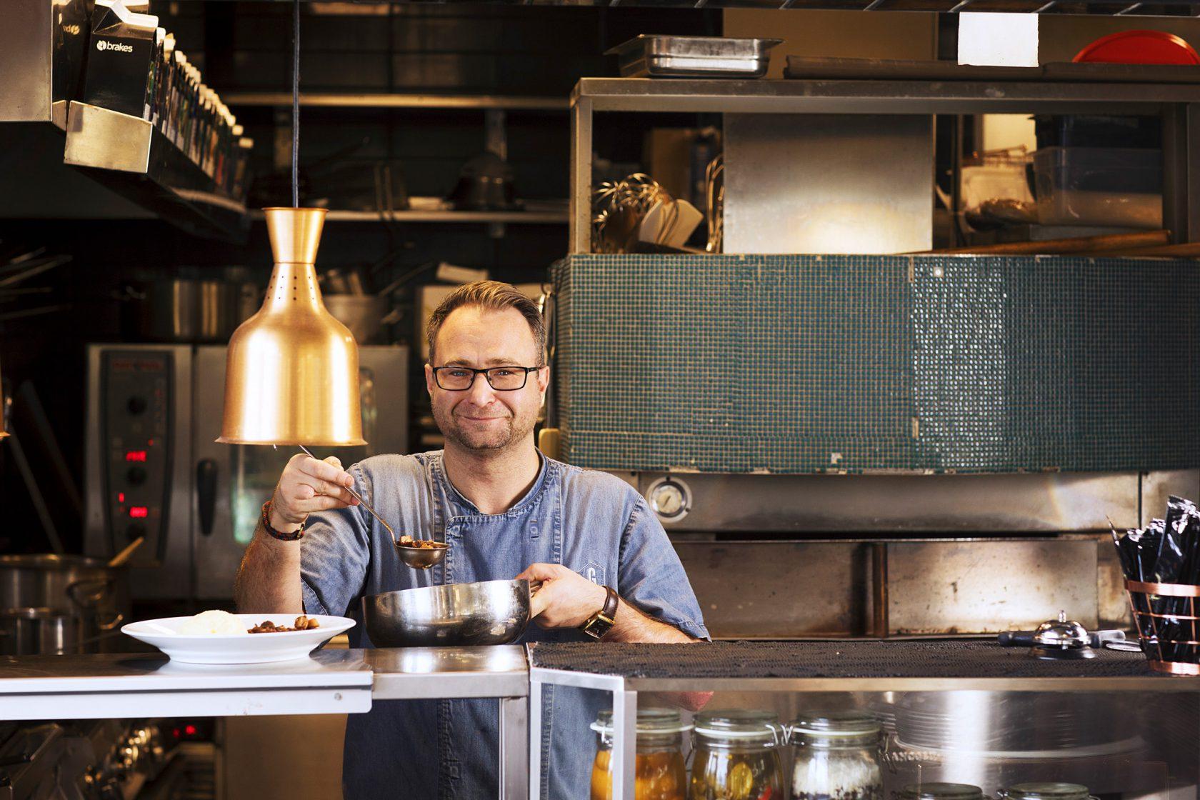 En leende man står bakom en restaurangdisk och lägger upp mat på en tallrik.