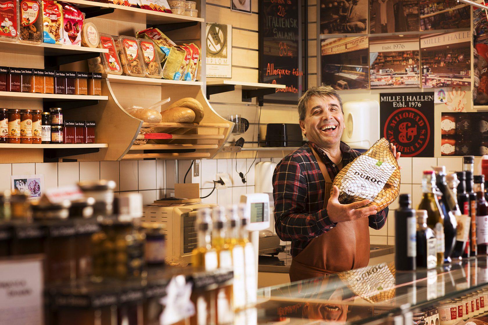 En skrattande man står bakom en butiksdisk och håller upp matprodukter.