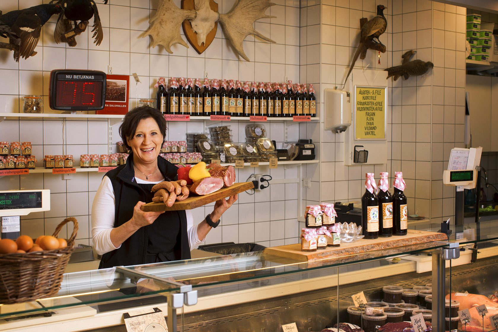 En kvinna står bakom en butiksdisk med en bricka med köttprodukter.