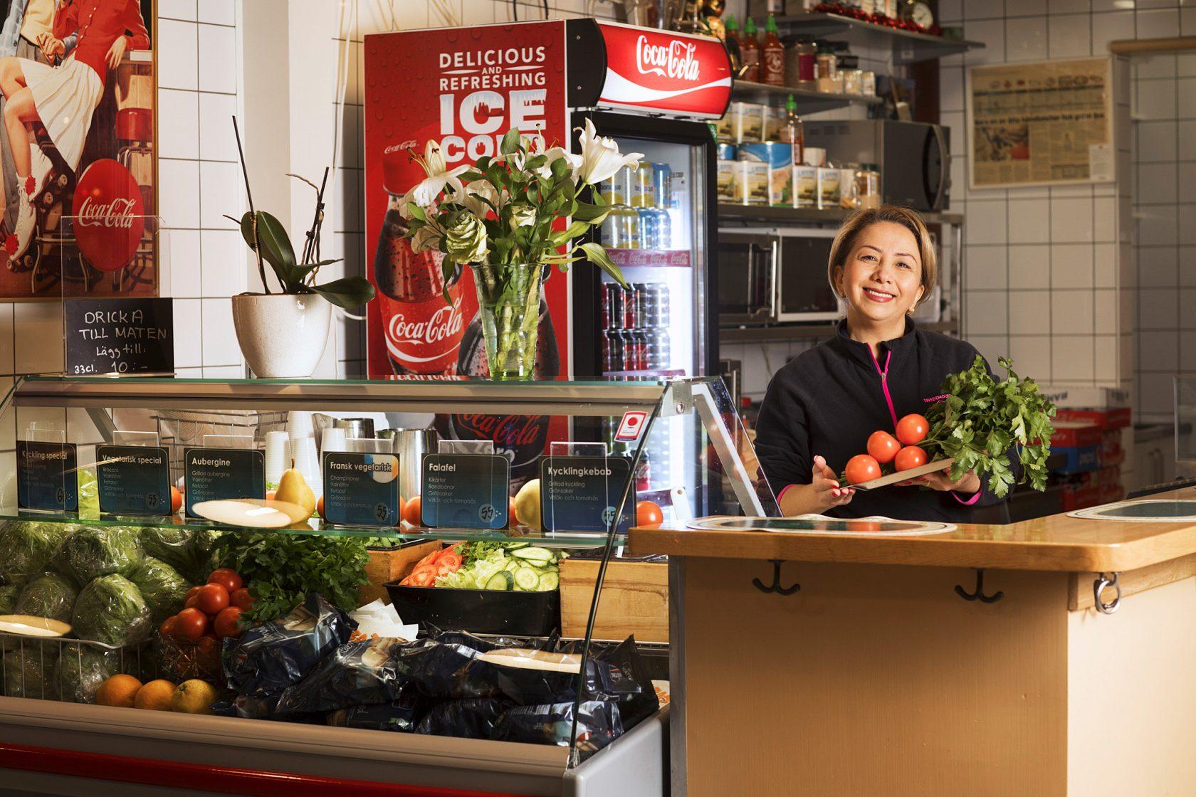 En kvinna i personalen står bakom en disk och håller upp ett knippe grönsaker.