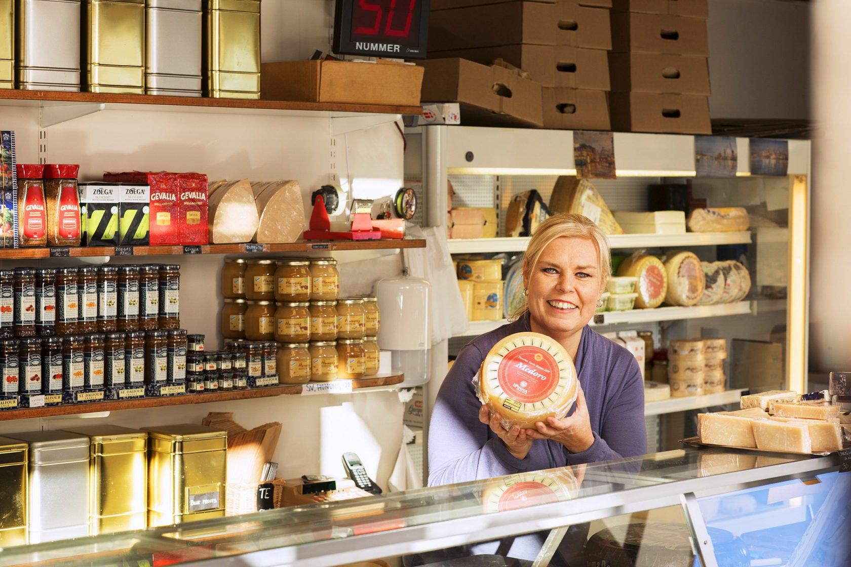 Kvinna bakom en disk står och håller upp en ost.