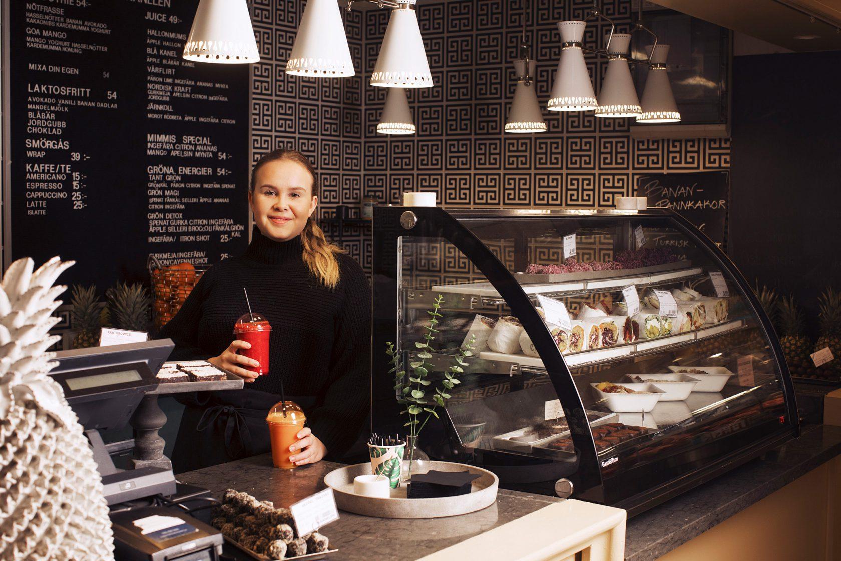 En kvinna i personalen står bakom en disk med en smoothie i handen.