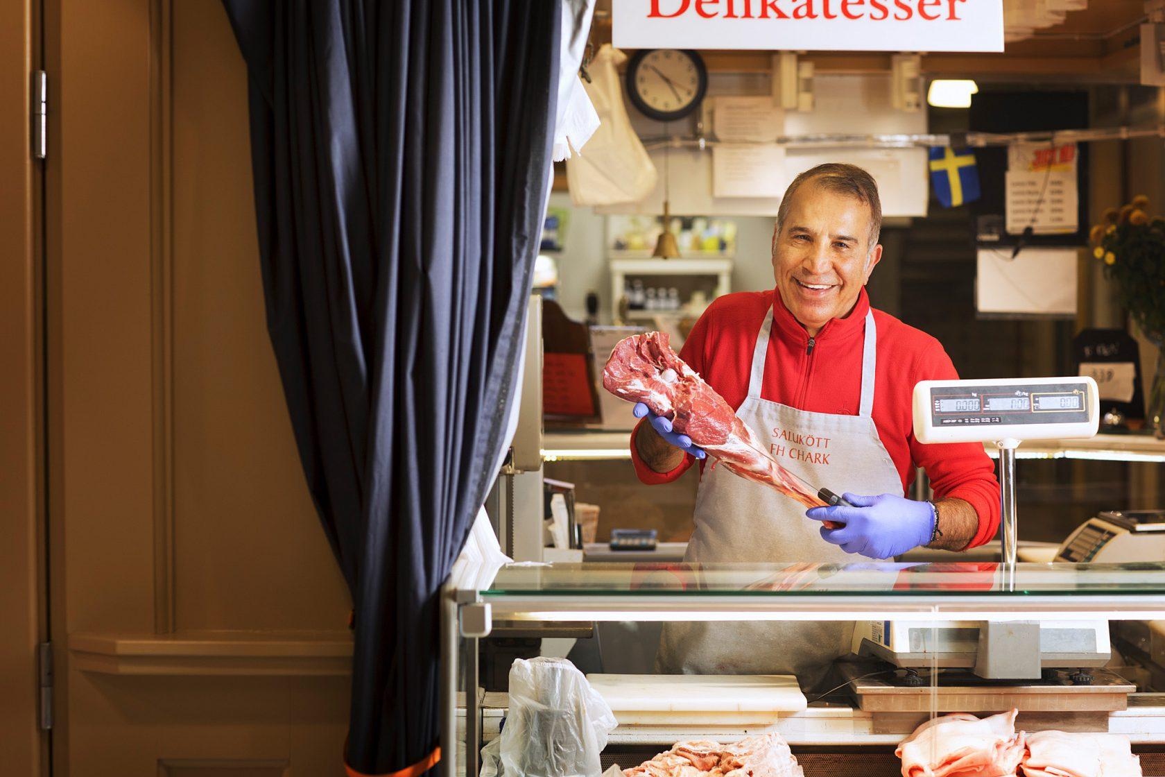 En man i personalen står bakom en disk med ett stycke kött i händerna.
