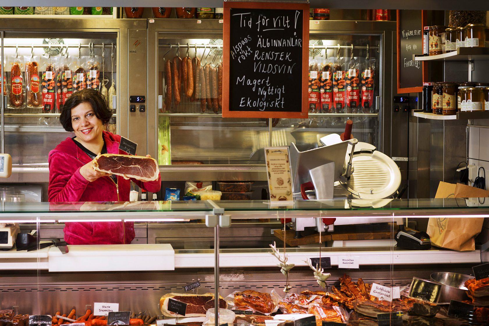 En kvinna i personalen står bakom en disk och håller upp sina matprodukter.