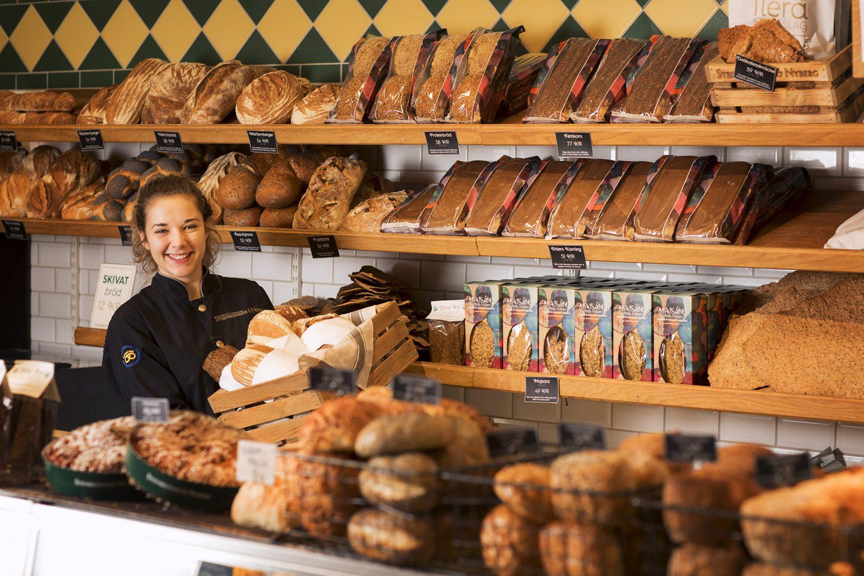 En leende kvinna står omgiven av bröd bakom en disk.