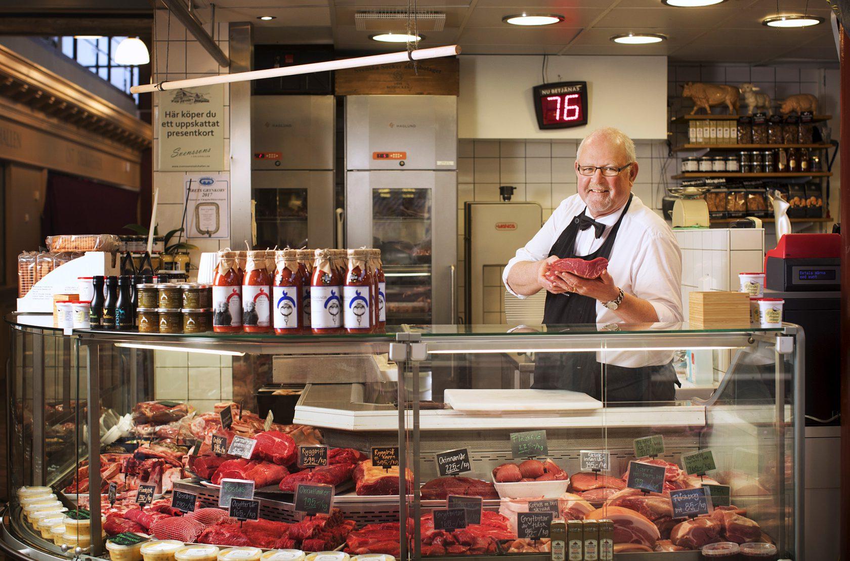 En man i personalen står bakom handlardisken med ett stycke kött i händerna.