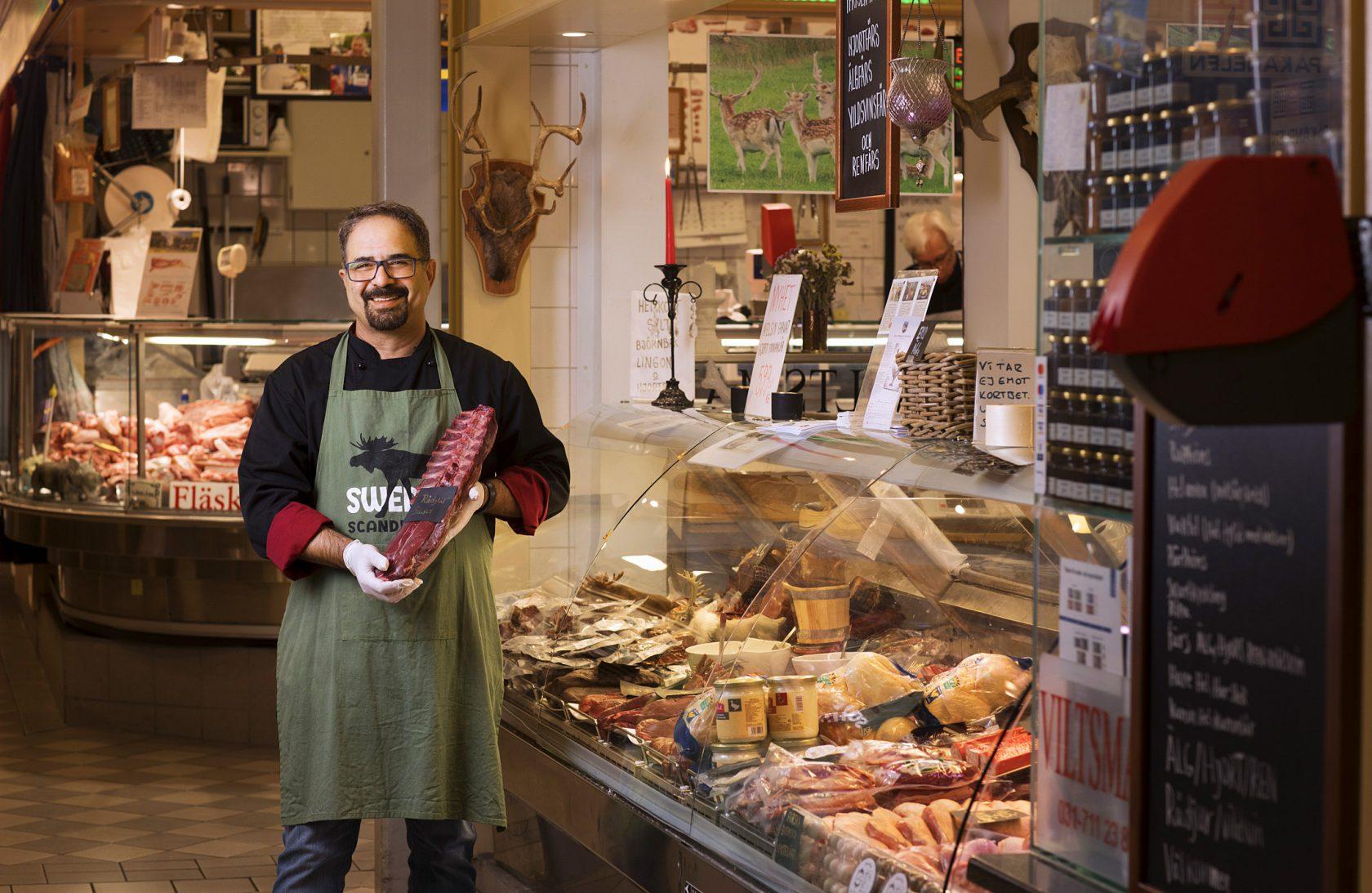 En man i personalen står framför sin handlarbod med ett stycke kött i händerna.