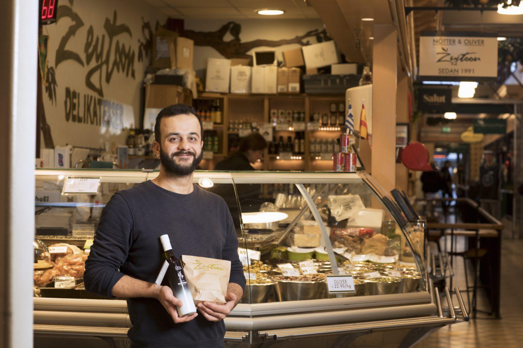 En man i personalen står framför sin handlarbod med mat produkter i handen.