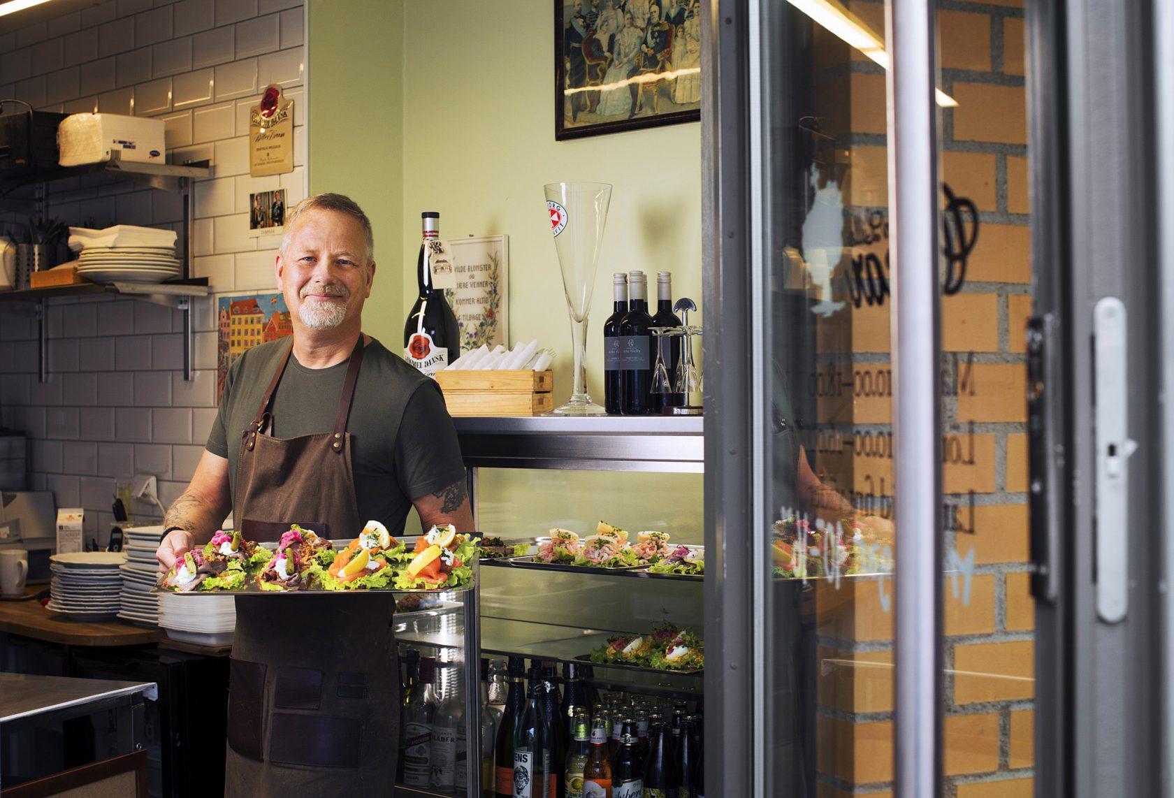 En man i personalen välkomnar till restaurangen med en bricka med smörrebröd.