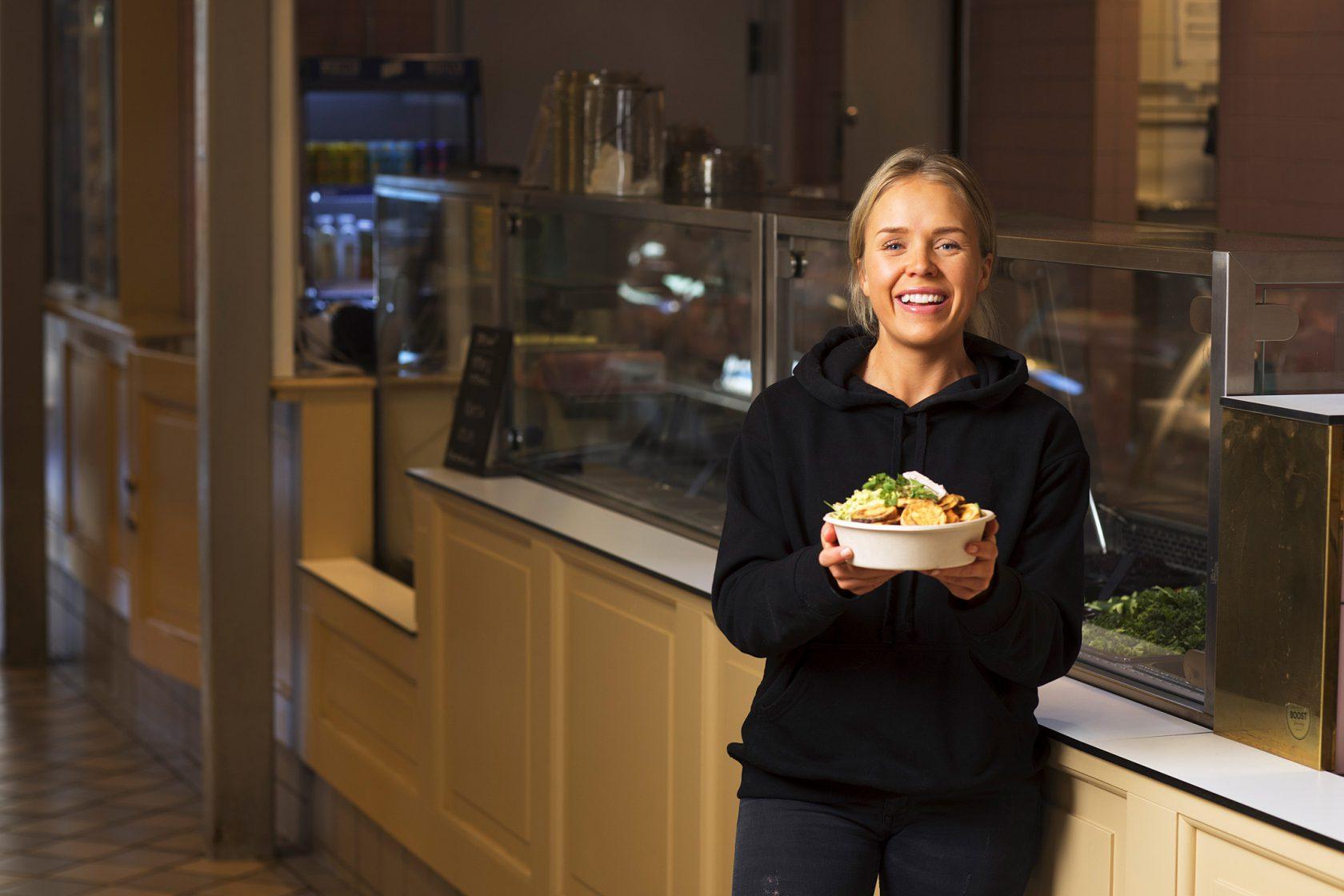 En kvinna i personalen står framför restaurangen med en skål med mat.