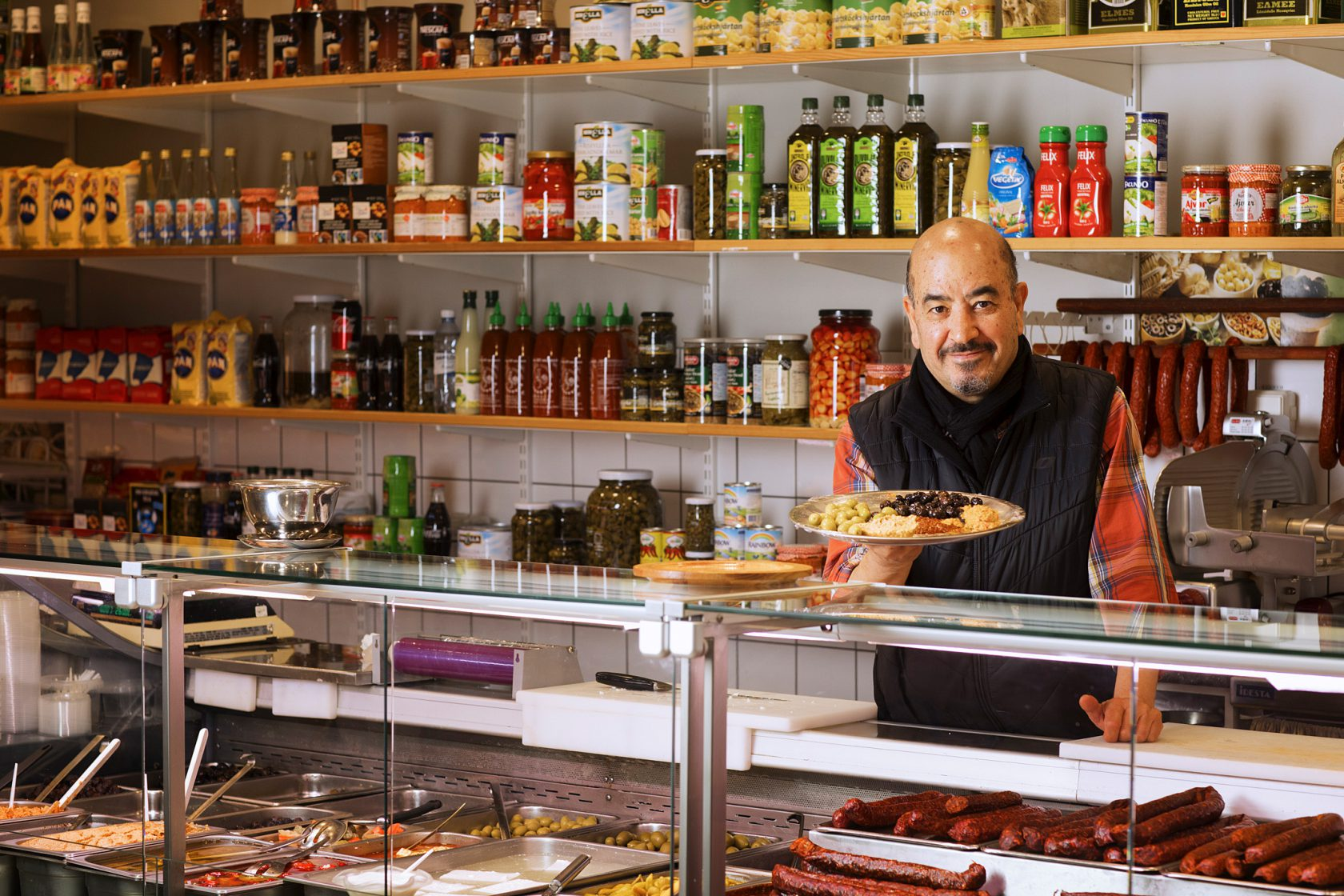 En man i personalen står bakom disken med en tallrik mat.