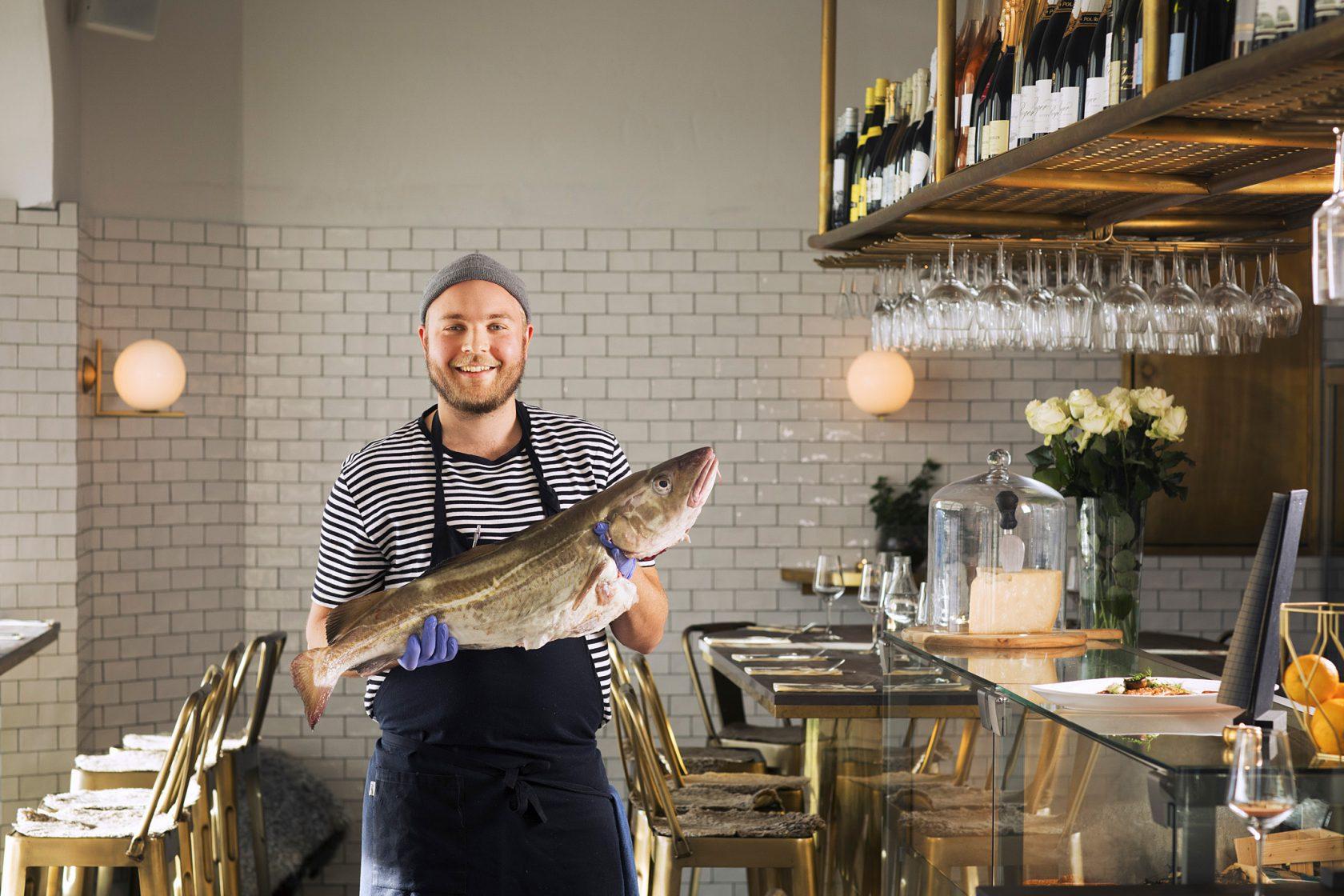 En glad man i personalen håller upp en stor fisk i restaurangen.