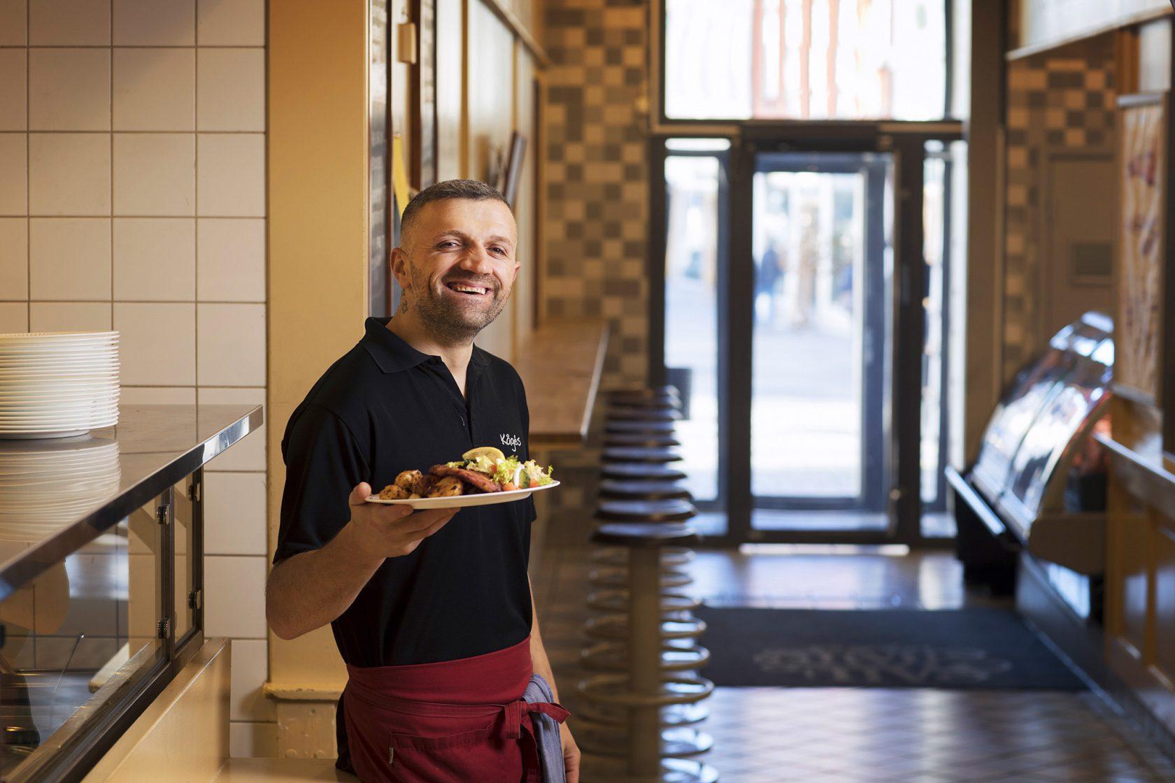 En man i personalen står med en tallrik mat framför restaurangen.