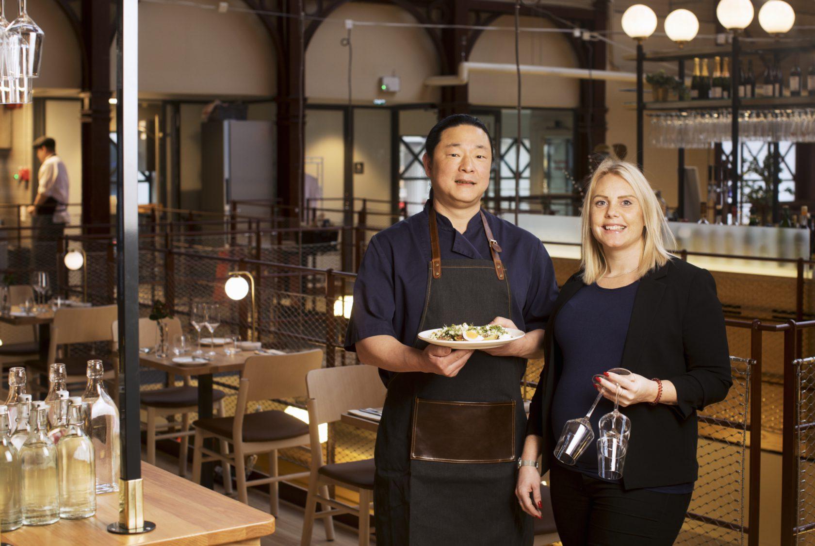 Restaurangpersonal står med en tallrik mat och två glas i handen.